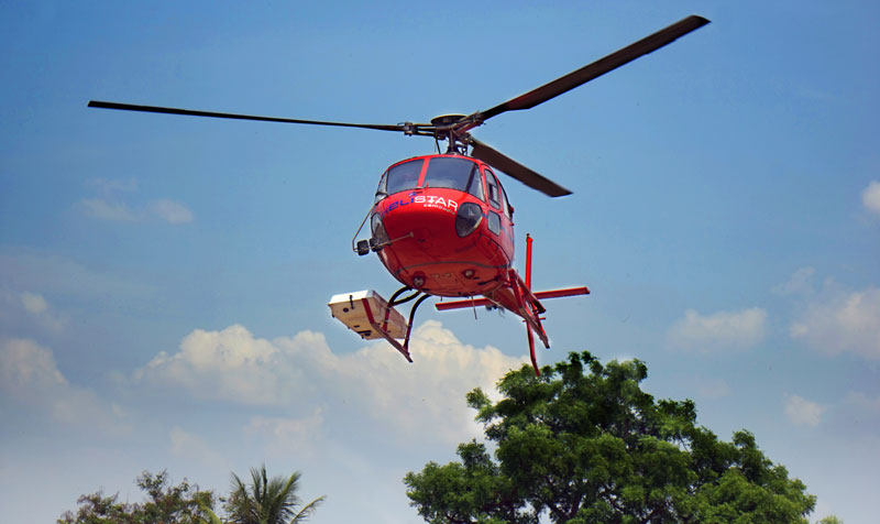 The helicopter during the 2015 flight operations, with the lidar instrument mounted within a pod on the right-hand skid.