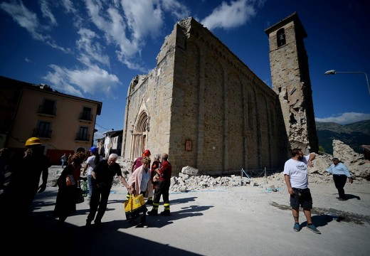 People walk past an earthquake damaged church during search and rescue operations in Amatrice on August 24, 2016 after a powerful earthquake rocked central Italy, leaving at least 240 people dead.