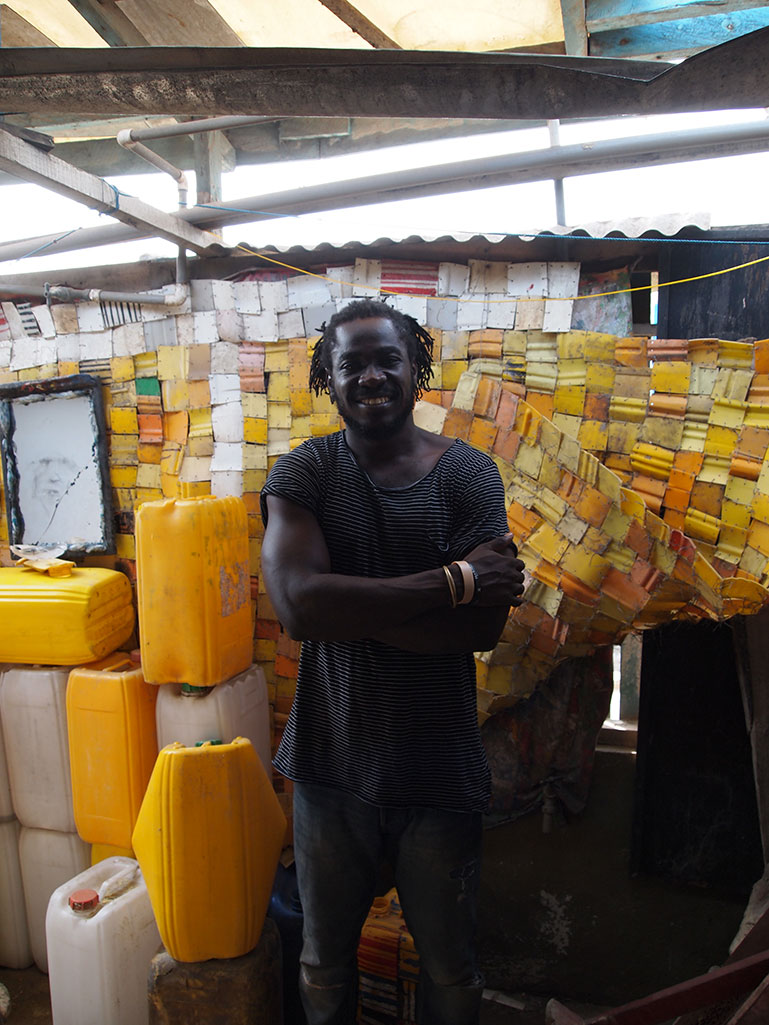 Serge Attukwei Clottey in his studio in front of some materials and unfinished works. Photo: Stephanie Dieckvoss